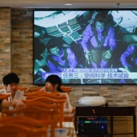 A TV broadcasts Chinese astronauts in the Shenzhou spacecraft, at a restaurant in Beijing on Friday. | AFP-JIJI
