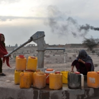 Women collect water on the outskirts of Jalalabad, Afghanistan, in February 2020.   AFP-JIJI