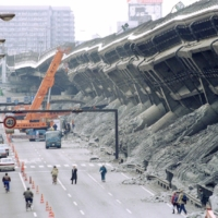 A giant crane pulls crushed cars out of debris in Kobe in January 1995.    REUTERS