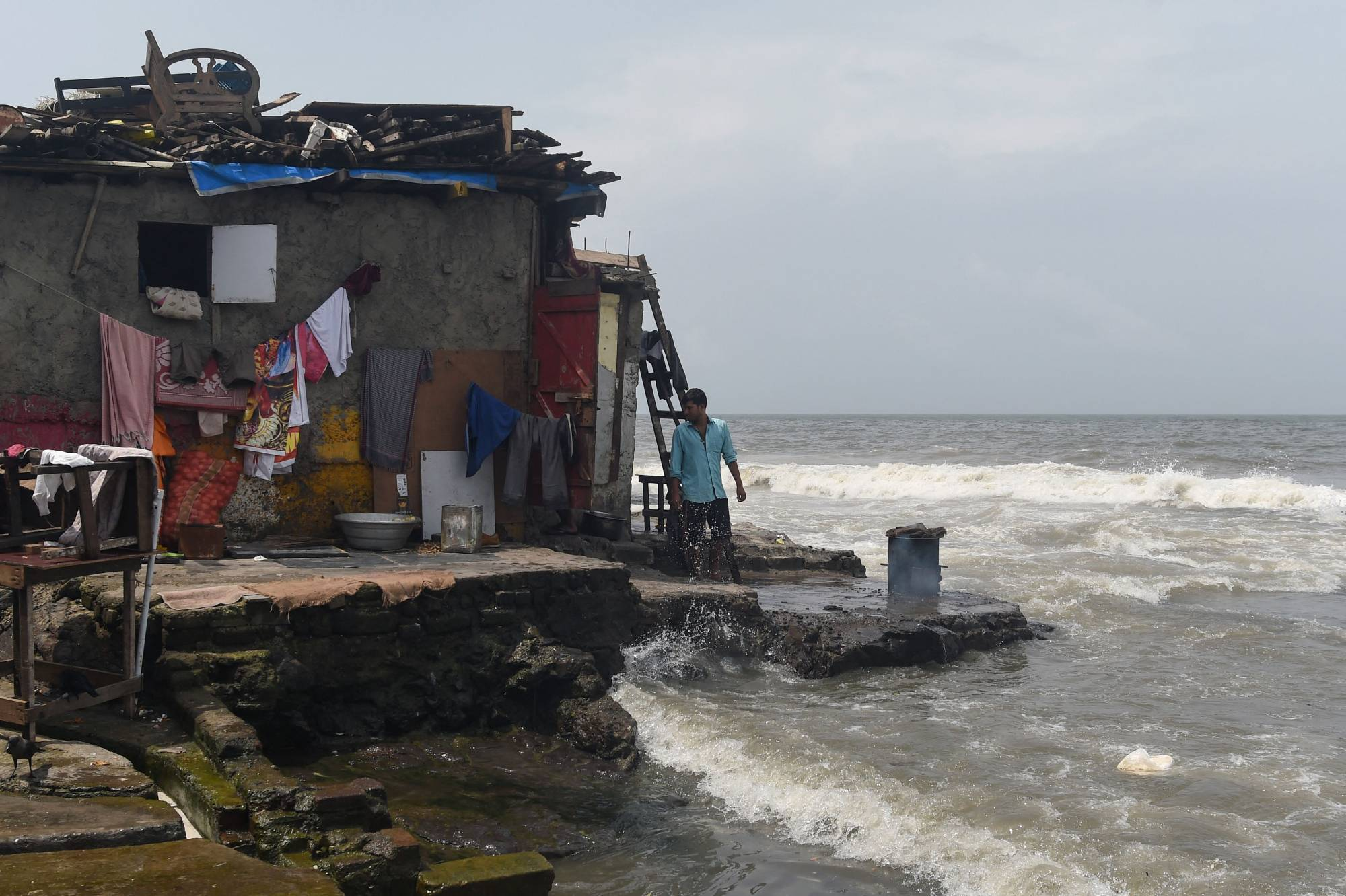 A home built next to the sea during high tide in Mumbai | AFP-JIJI