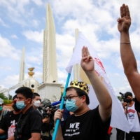 Protest leader Parit 'Penguin' Chiwarak (center) shows a three-finger salute during a demonstration in Bangkok on Thursday to mark the 89th anniversary of the abolition of absolute monarchy.   | REUTERS