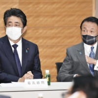 Former Prime Minister Shinzo Abe and Finance Minister Taro Aso attend a meeting of a parliamentary group on semiconductors at the Diet on May 28. | KYODO