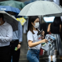 A woman protects her copy of the Apple Daily's final issue from the rain after lining up to buy it from a newsstand in Hong Kong on Thursday.    AFP-JIJI