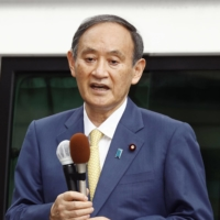 Prime Minister Yoshihide Suga speaks at the Liberal Democratic Party headquarters in Tokyo Friday as official campaigning for the Tokyo Metropolitan Assembly kicked off. | KYODO