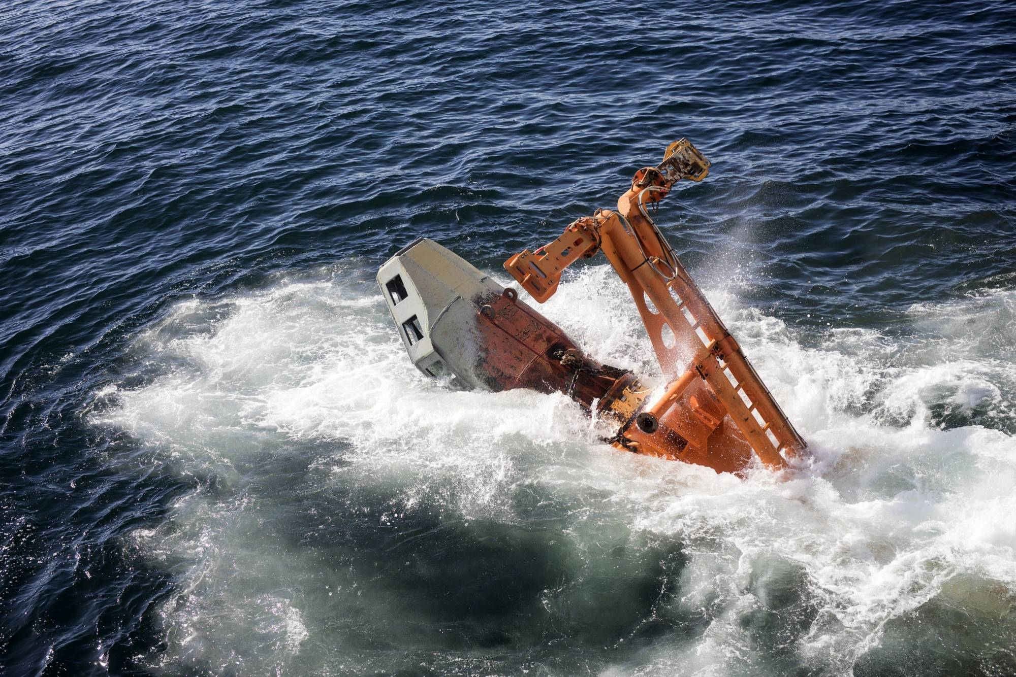 The suction rig of a 'crawler' tractor drops into the sea from the deck of the Mafuta diamond mining vessel off Namibia. | BLOOMBERG