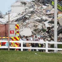 Emergency crew members search for missing residents on Thursday. | REUTERS