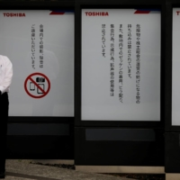 A staff member stands in front of the venue of Toshiba Corp's annual general meeting with its shareholders in Tokyo on Friday.  | REUTERS
