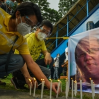 Supporters of the late President Benigno Aquino light candles during a prayer vigil outside a university where his remains lay on Friday.  | AFP-JIJI