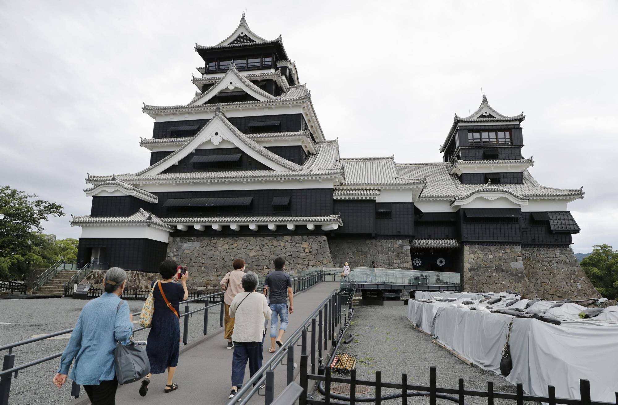 Visitors head for the main tower of Kumamoto Castle, which reopened to the public Monday after undergoing repairs following massive earthquakes in 2016.   KYODO