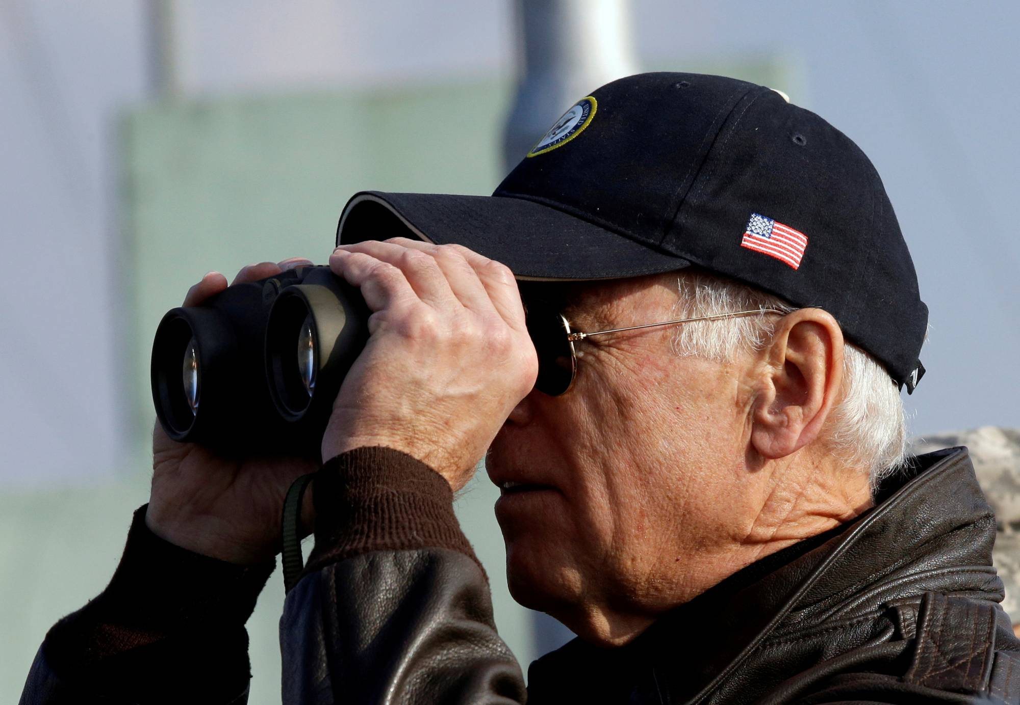 Then-U.S. Vice President Joe Biden looks through binoculars to see North Korea from Observation Post Ouellette during a tour of the Demilitarized Zone, the military border separating the two Koreas, in Panmunjom, South Korea, in December 2013. | POOL / VIA REUTERS