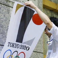 An official removes an Olympic poster with Kenjiro Sano's controversial logo from a wall of the Tokyo Metropolitan Government building in September 2015.   KYODO