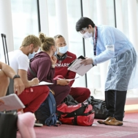 Members of the Danish Olympic rowing team fill in documents after their arrival at Tokyo's Haneda Airport on June 20. | KYODO