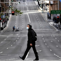 A man walks along the main road in Sydney on Saturday, as Australia's largest city entered a two-week lockdown to contain an outbreak of the highly contagious Delta variant.  | AFP-JIJI