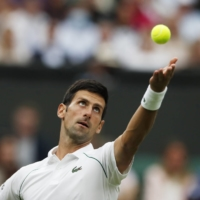 Novak Djokovic serves the ball during his Wimbledon first-round match against Jack Draper on Monday in London. | REUTERS