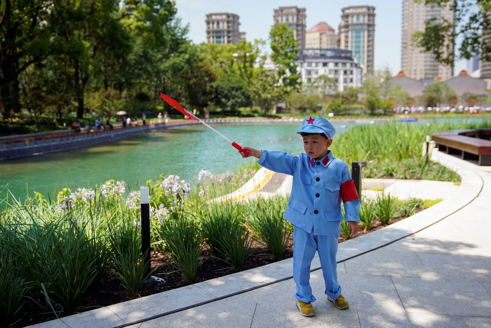 A boy dressed in a replica uniform of the Red Army poses with a Chinese flag outside the Memorial of the First National Congress of the Communist Party of China in Shanghai on June 22. | REUETRS