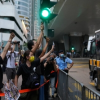 Supporters gesture toward a prison van outside the West Kowloon Magistrates' Courts in Hong Kong in May, after a court hearing attended by pro-democracy activists over charges related to the national security law. | REUTERS