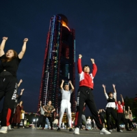 Residents exercise at a park in front of a 328-metre tower that houses a five-star hotel, aquarium and presidential suites in the village of Huaxi.   AFP-JIJI