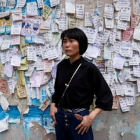 Jade Chung, a freelance journalist whose work focuses on human rights and pro-democracy activists, poses for a photograph in front of a wall covered with ads at Kwun Tong in Hong Kong in May.    REUTERS