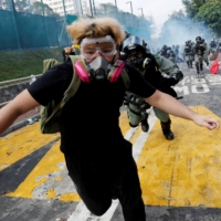 A university student runs from riot police at the Chinese University of Hong Kong in November 2019.    REUTERS