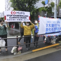 Environmental activists call on Mitsubishi UFJ Financial Group to take on a climate change resolution, near the venue of its annual general shareholders meeting in Tokyo on Tuesday. The resolution was voted down. | KYODO