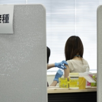 A Suntory Holdings Ltd. employee receives a dose of the Moderna COVID-19 vaccine at a vaccination site at the company's office in Tokyo on June 21. | BLOOMBERG