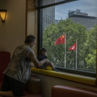 The Flags of China and Hong Kong fly outside the Central Library in Hong Kong in June.  | LAM YIK FEI / THE NEW YORK TIMES