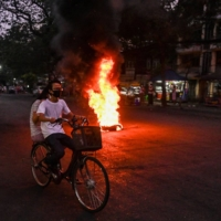 People cycle past a burning makeshift barricade, erected by protesters demonstrating against the military coup, in Yangon in April. With bars shuttered, universities empty and hook-up apps poleaxed by internet blackouts, dating got much harder in post-coup Myanmar, but young people are still finding love — often in the heady rush of anti-junta protests.   AFP-JIJI