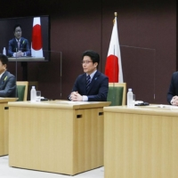 Chief Cabinet Secretary Katsunobu Kato (left) takes part in an online symposium on the issue of North Korea's abductions Tuesday along with Takuya Yokota (center), the younger brother of the kidnapped Megumi Yokota, and Koichiro Iizuka, the eldest son of Yaeko Taguchi, who was abducted in around June 1978.   KYODO