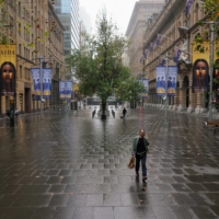A woman walks through a quiet square in Sydney on Wednesday.  | REUTERS