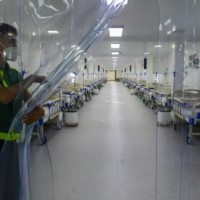 A worker holds a plastic divider inside a field hospital for Covid-19 patients at a park in Manila on June 24.    AFP-JIJI