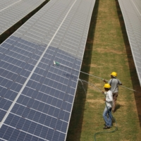 Workers clean photovoltaic panels at a solar power plant in Gujarat, India, in 2015. | REUTERS