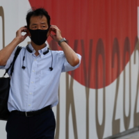 A man wearing a protective mask walks past a sign for the 2020 Tokyo Olympics in the capital on Wednesday. | REUTERS