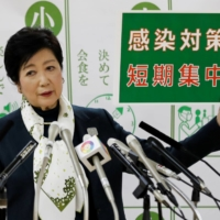 Tokyo Gov. Yuriko Koike holds a placard reading 'short-term intensive infection control measures,' a slogan relating to the city's response to the coronavirus outbreak, at a news conference in Tokyo on Nov. 25.   REUTERS