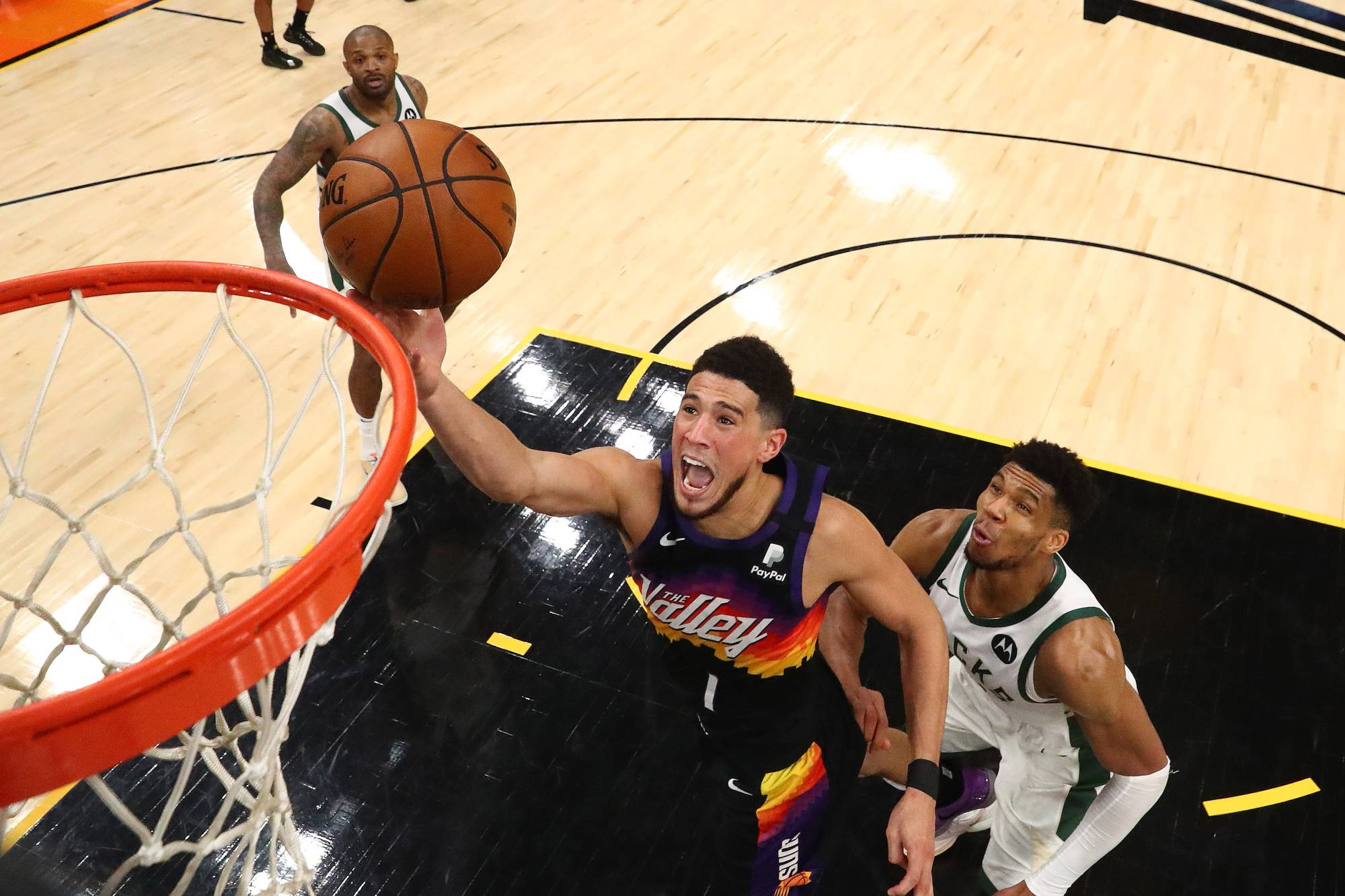 Suns guard Devin Booker shoots the ball past Bucks forward Giannis Antetokounmpo during Game 5 of the NBA Finals at Phoenix Suns Arena on Saturday.  | USA TODAY / VIA REUTERS