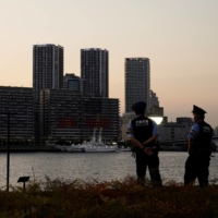 Police officers stand guard near the 2020 Tokyo Olympic athletes' village, where a growing number of athletes and staff have tested positive for COVID-19. | REUTERS