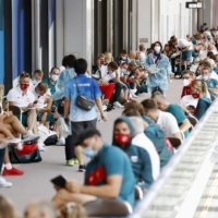 Olympic athletes and staff wait to be tested for COVID-19 at Narita Airport on arrival Sunday. | KYODO