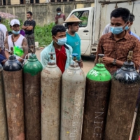 People wait to fill up empty oxygen canisters outside a factory in Yangon, Myanmar, on July 14, amid a surge in COVID-19 cases.  | AFP-JIJI