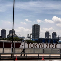 A man passes by a Tokyo 2020 panel Tuesday, three days prior the opening ceremony of the Olympic Games. | AFP-JIJI