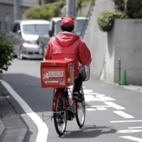 Japan's stay-at-home stocks, including those of food-delivery operators, are seen as more likely to get a boost from the Games, according to analysts. | BLOOMBERG