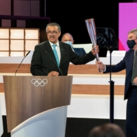 World Health Organization Director-General Tedros Adhanom Ghebreyesus receives the Olympic torch from International Olympic Committee President Thomas Bach during the second day of an IOC meeting in Tokyo on Wednesday.    GREG MARTIN / IOC / VIA AFP-JIJI