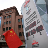 A woman holds a Chinese national flag next to a countdown clock showing 200 days left until the opening of Beijing Winter Olympics in the city on Monday. The Games will need spectators to be successful, the International Olympic Committee said on Wednesday.   REUTERS