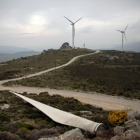 A flap of a destroyed wind turbine on the ground as other wind turbines operate on a mountain top on the island of Evia, Greece | REUTERS