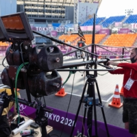 Staff members of Olympic Broadcasting Services set up equipment in Tokyo on Monday.  | AFP-JIJI