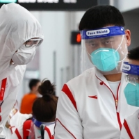 Chinese Basketball Association President Yao Ming (center) stands with staffers during the quarantine process after arriving at Narita Airport in Chiba Prefecture on July 19 ahead of the Tokyo Games. | REUTERS