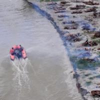 Disaster response team members patrol the Ganges River, past burning funeral pyres of bodies that washed up on its banks after monsoon rains swelled it and exposed shallow sand graves dug during the peak of a COVID-19 wave in Phaphamau, on the outskirts of Prayagraj, India, on June 25. | REUTERS