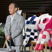 Prime Minister Yoshihide Suga speaks to reporters at the Prime Minister's Office in Tokyo Wednesday, with the Olympic official mascots behind him.  | KYODO
