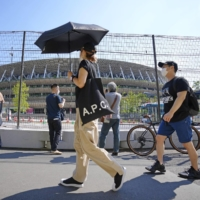 Pedestrians walk in front of the National Stadium in Tokyo on Thursday.   KYODO