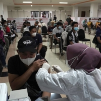 A health care worker administers a dose of the AstraZeneca COVID-19 vaccine in Jakarta in May.    BLOOMBERG