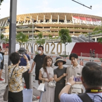 People take pictures in front of the National Stadium on Thursday, a day before the opening ceremony of the Tokyo Olympics.   KYODO