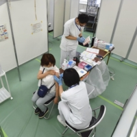 A woman is inoculated against COVID-19 at a mass coronavirus vaccination center run by the Self-Defense Forces in the Otemachi business district of Tokyo in May.   POOL / VIA KYODO